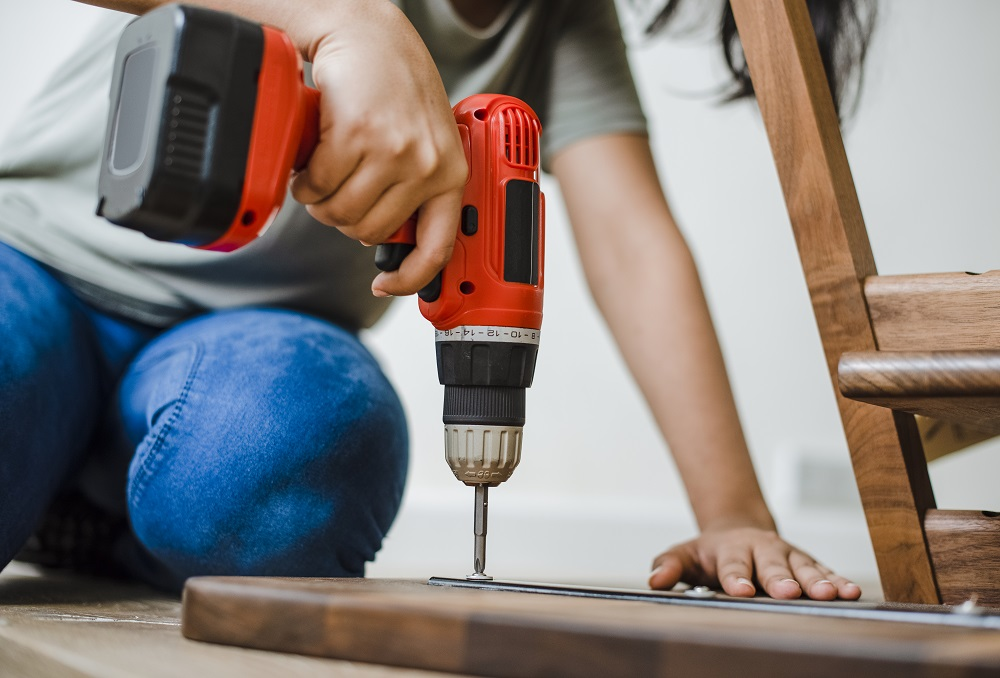 Woman using hand drill to assemble a wooden table